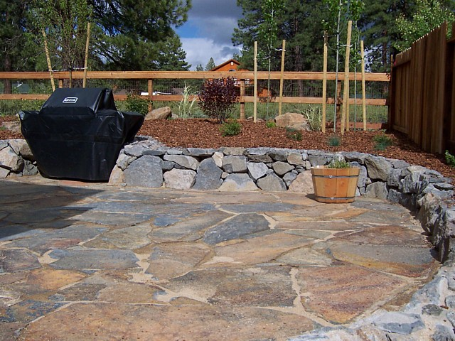 Flagstone patio with rock wall for Flagstone patio designs
